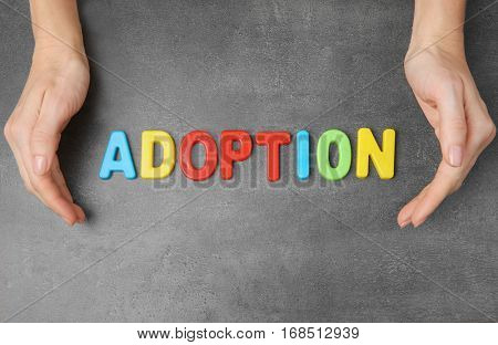 Female hands and word ADOPTION on grey textured background