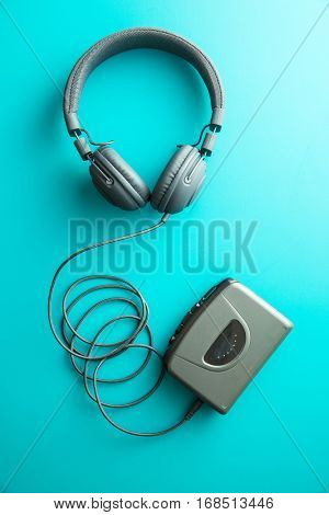 The vintage audio player and headphones on blue background. Top view.