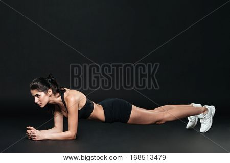 Beautiful focused fitness woma standing in plank position over black background