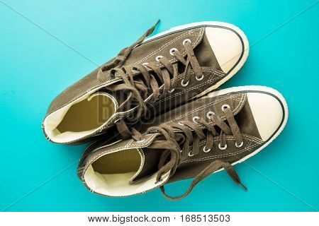 The vintage sneakers on blue background. Top view.