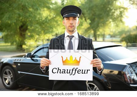 Young man standing with banner CHAUFFEUR near luxury car outdoor