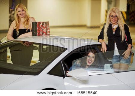 Three laughing women, one sits on driver seat and another two stand near modern white car at underground parking.