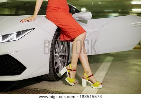 Woman in orange dress and high-heel shoes sits on hood of modern white car at underground parking.