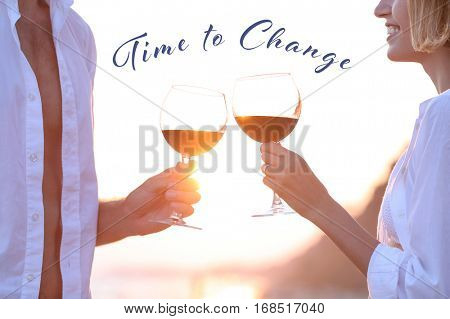 Young couple drinking red wine on seashore. Text TIME TO CHANGE on background