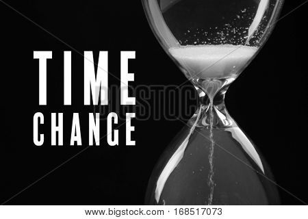 Hourglass and text TIME CHANGE on black background