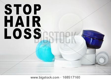 Text STOP HAIR LOSS on background. Set of cosmetic products on white wooden table
