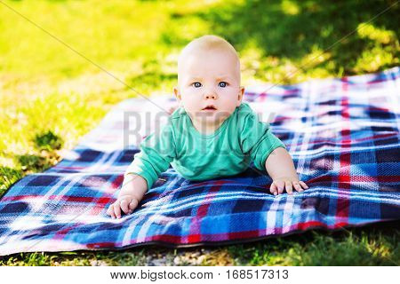 Cute Child Baby Boy Lying On Blanket In Summer Day On Nature