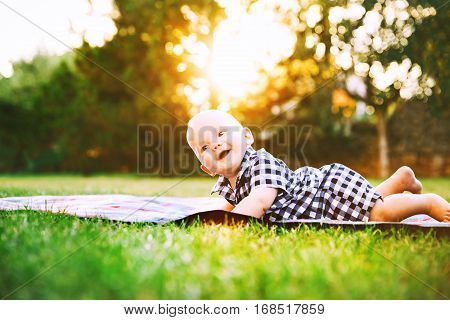Cute  Adorable Child Baby Boy Lying On The Grass On Nature
