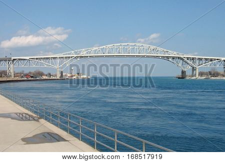 The two spans of the Blue Water International Bridge carry traffic across the St. Clair River near its juncture with Lake Huron. Port Huron Michigan USA is on the left and Sarnia Ontario Canada is on the right.