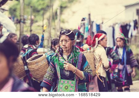 SAPA, VIETNAM - OCTOBER 29, 2012: Hmong women sell souvenirs in Sapa. The Hmongs are known for their colorful clothes and silver jewelry. Hmong women have various clothes colours and style