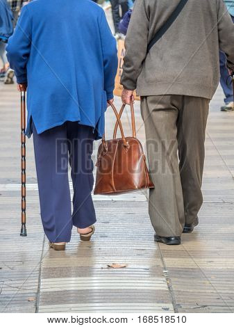an elderly couple carrying a bag together. picture symbolizing love aged