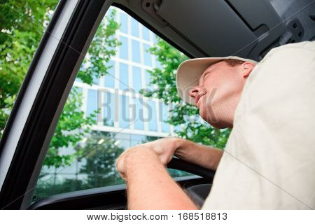 a delivery person is driving his van and looking up at a skyscraper