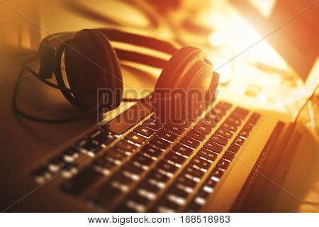Listening Music While Working. Laptop Computer and Modern Headphones Closeup Photo. Reddish Warm Colors.