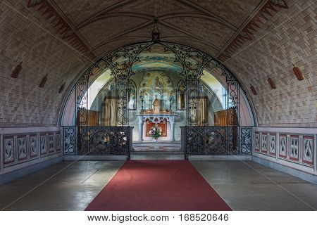Orkneys Scotland - June 5 2012: The empty nave leads to the chancel with altar and wall paintings in Italian Chapel on Lamb Holm Island. Wine-red carpet colorful reredos natural light domed ceiling.