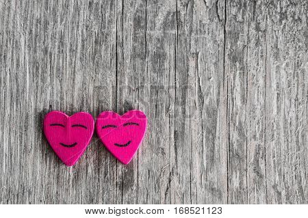 Two smiling pink hearts on wooden background, relationship valentines day concept