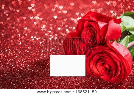 Three beautiful red roses and blank card on glitter background vith bokeh hearts