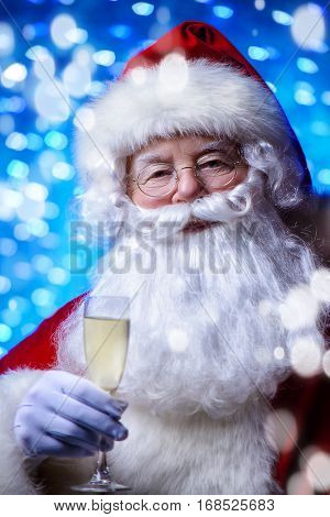 Santa Claus wishes you a Happy New Year and Merry Christmas. Holiday lights in the background.