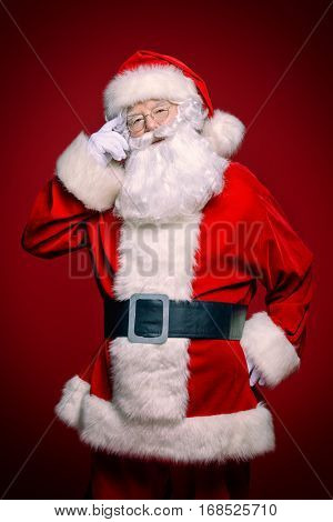 Christmas concept. Portrait of a fairytale Santa Claus over red bakground. Good old traditions. Family holidays.