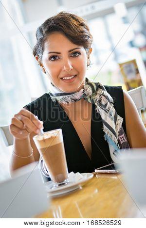 Middle eastern woman stirring coffee