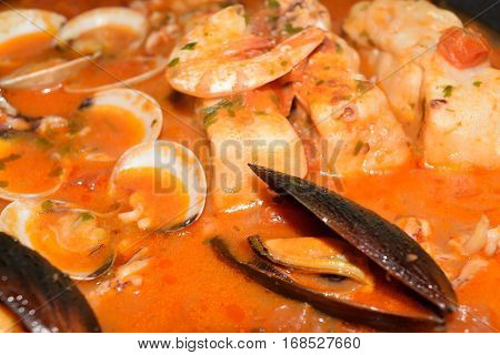 Tasty fish soup with cod shrimp mussels and other mollusc