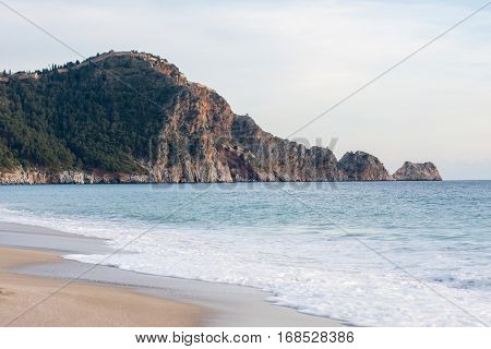 Castle Rock of Cleopatra beach in Alanya Turkey with sea and sand on front plan and rock covered with pine forests on bacground