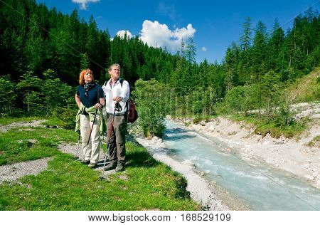 a senior couple is hiking in berchtesgaden bavaria, germany and enjoying the magnificent landscape