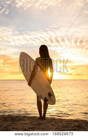 Beach sunset sexy surfer woman surfing lifestyle relaxing holding surfboard looking at ocean for surf. Active healthy living silhouette of sports athlete standing waiting for waves.