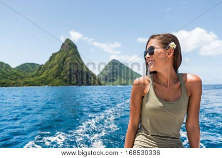 Happy woman cruising towards the deux gros pitons, popular tourist attraction in St Lucia. World Heritage site. Young traveler relaxing on shore excursion boat tour from cruise ship vacation travel.