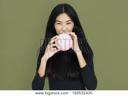 Young asian woman casual blowing a balloon