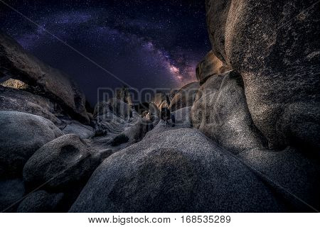 Photographer doing astro photography in a desert nightscape with milky way galaxy. The background is stary celestial bodies in astronomy. The heaven depicts science and the divine. poster