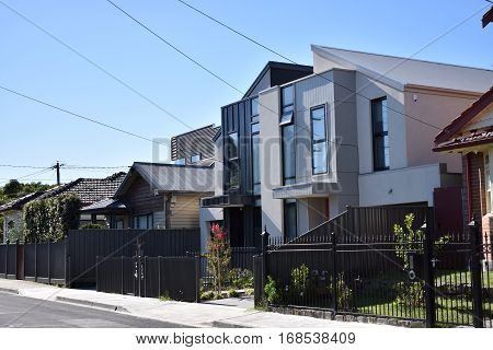 suburban streetscape of modern houses against blue sky