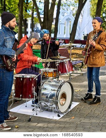 Festival music band. Friends playing on percussion instruments in city park. Fountain and trees in the background.