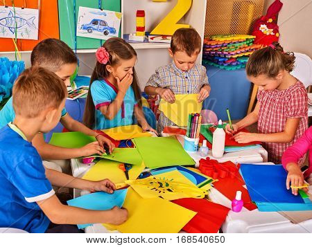 Child cutting paper in class. Kids development and social lerning children in school. Children's project in kindergarten. Pictures into background