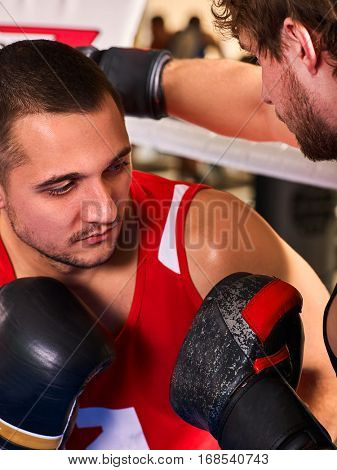 Boxing ring with two men boxer. Man engage in martial arts. Sportsman do fitness wearing helmet and gloves boxing . Close up of testing of fighting techniques indoor