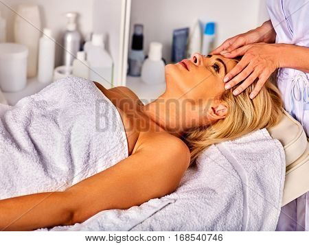 Facial massage for forty year old woman. Portrait of woman middle-aged take face cleaning in spa salon.