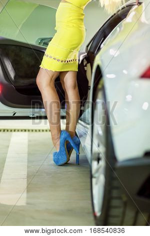 Legs in blue high-heel shoes of woman in yellow dress standing near modern white car.