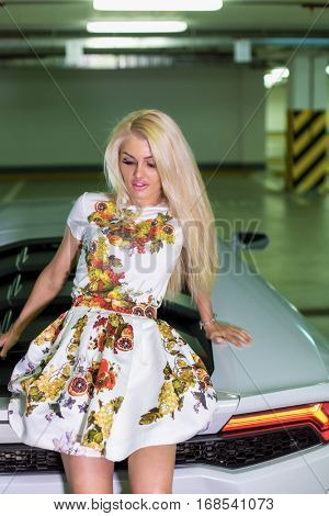 Young woman in flowery dress sits on hood of modern white car at underground parking.