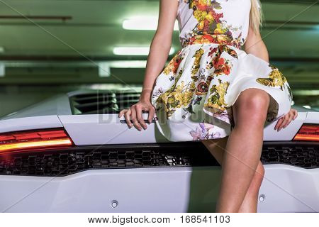 Body and leds of young woman in flowery dress sitting on hood of modern white car at underground parking.