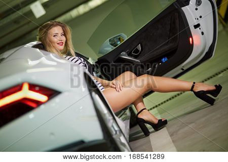 Young blonde woman in striped bodysuit and high-heel shoes poses sitting on passenger seat of modern white car at underground parking.