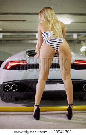Young blonde woman in striped bodysuit and high-heel shoes poses leaning hands on trunk of modern white car at underground parking, rear view.