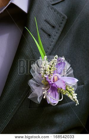 boutonniere flower in the pocket of the groom on wedding ceremony