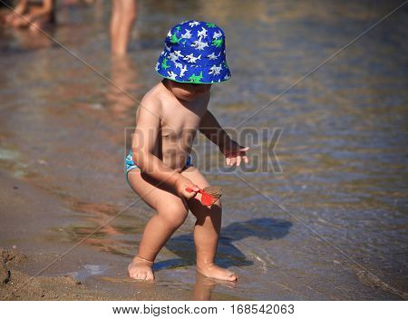 DIDIM TURKEY - JULY 9 2014. Baby boy playing with toys on the sea.