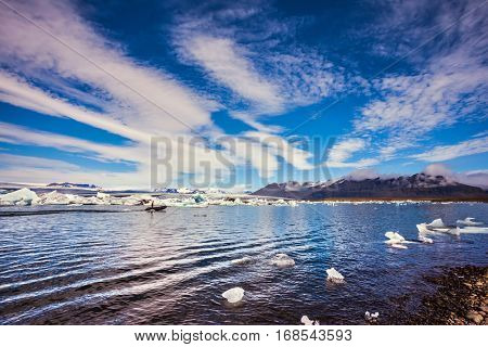 The ice floes and cirrocumulus clouds of lagoon Jokulsarlon, Iceland. Clouds reflected in the water of lagoon. The concept of northern extreme tourism