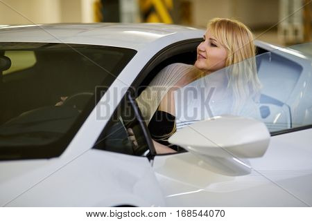 Young blonde woman looks out from driver seat of modern white car at underground parking.