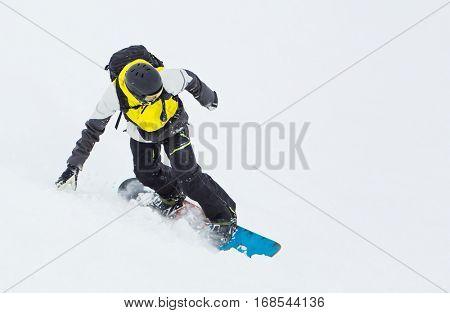 Active man snowboarder riding on slope, snowboarding closeup.