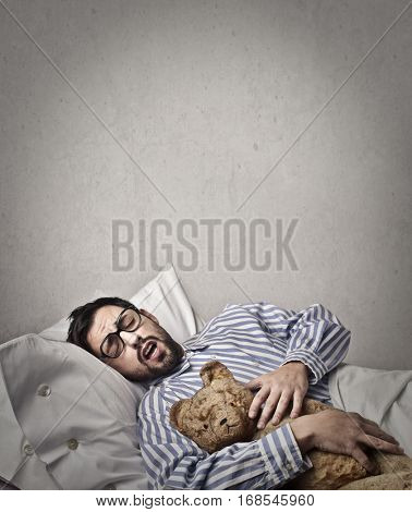 Man with nerdy glasses sleeping with his teddy bear deeply with the mouth open