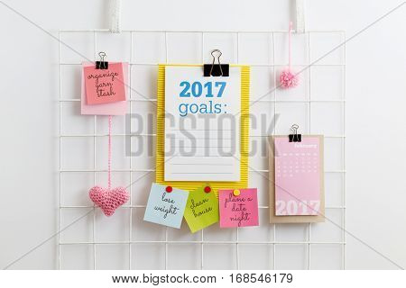 New Year's Resolutions. Paper note written with 2017 GOALS on diy metal mesh grid wall organizer. Metal grid display with pink heart and pom pom.