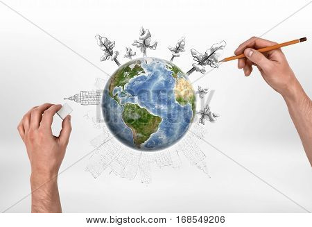 Male hands drawing trees with a pencil around the globe and erasing buildings with a rubber, on the white background. Ecology and Urbanization. Creativity and art. Environmental issues. Elements of this image are furnished by NASA.