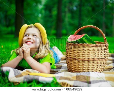 happy child with bananas and a fruit basket in the park outdoor