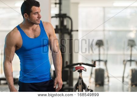 Fitness Model In Undershirt Flexing Muscles